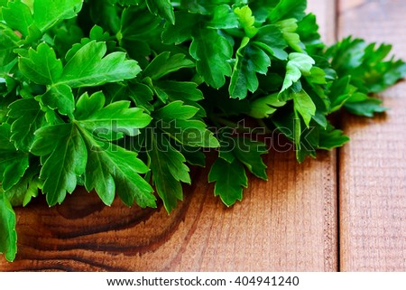 Parsley leaves closeup on wooden table - stock photo