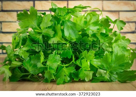 parsley on a wooden board on a brick background