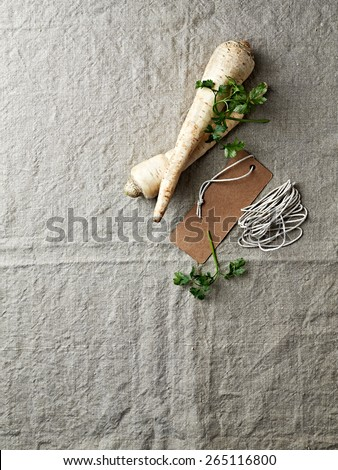 Parsley roots and  paper label on a linen cloth - stock photo