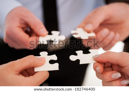 Part and parcel of business. Close-up of many people holding puzzle elements close to each other - stock photo