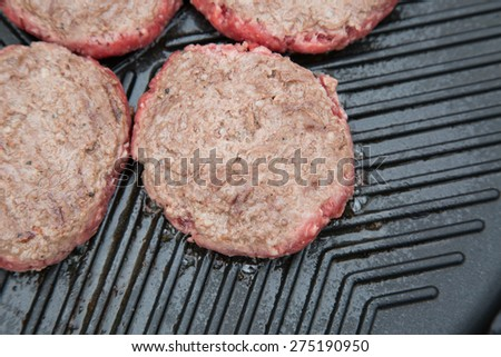 Part cooked burgers on a metal griddle - stock photo