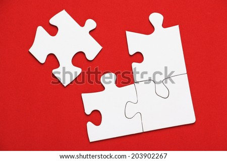 Part of a blank white jigsaw puzzle on bright red paper background