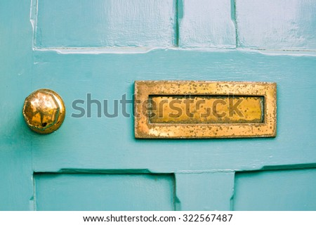 Part of a blue front door with a weathered metal letterbox