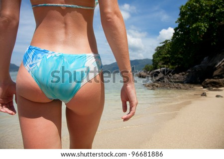 Part of a body of a young woman after lying on sand on sea background