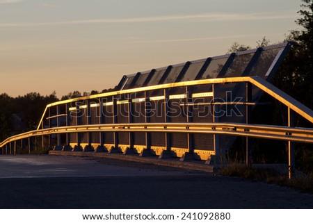 Part of a bridge in sunset. Bridge railing reflecting sunbeams. Bridge railing in silhouette, colorful background. - stock photo