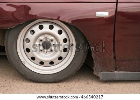 Part of a brown car with pneumatic suspension on the pavement. Car wheel, closeup