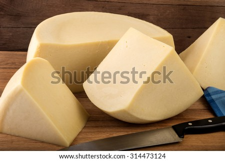 Part of a cheese wheel and pieces on a wooden background. - stock photo