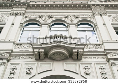 Part of a classic large stone building in London with arches and statues - stock photo