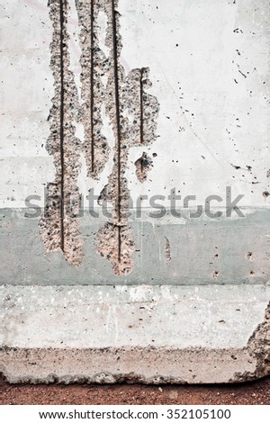 Part of a damaged old wall with exposed masonry and supporting metal rods - stock photo