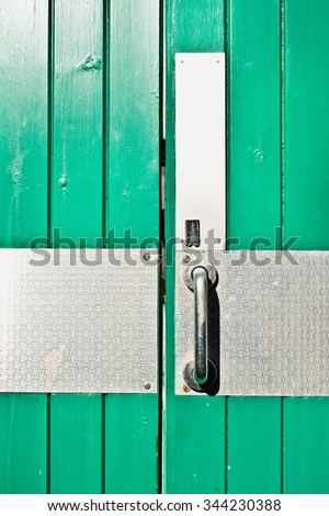 Part of a double green wooden door with metal plates and handle, for security - stock photo