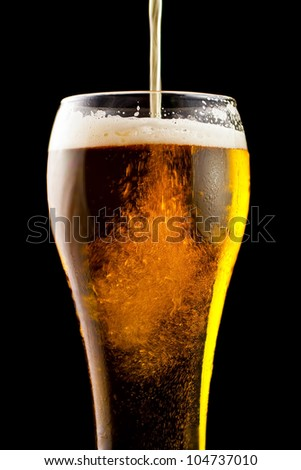 Part of a glass of cold beer is a light froth. - stock photo