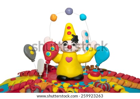 Part of a homemade birthday cake with a clown and balloons isolated on white