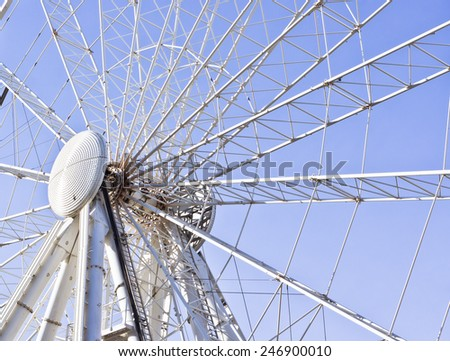 Part of a large modern big wheel against a blue sky - stock photo