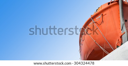 Part of a lifeboat with a large free space to the left as a sky. - stock photo