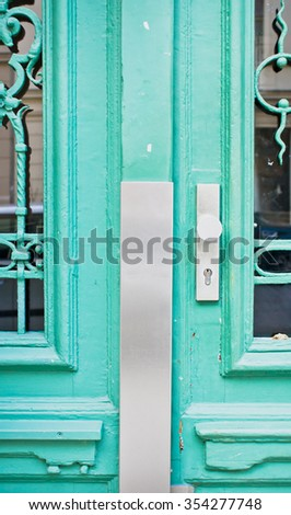 Part of a locked turquoise door with decorative bars - stock photo