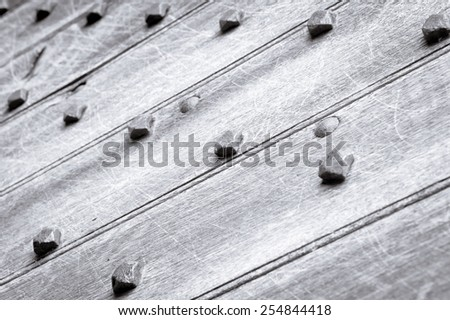 Part of a medieval door with metal studs in black and white - stock photo