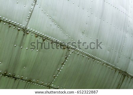 Part of a military aircraft. Rivets on the wing of the plane.