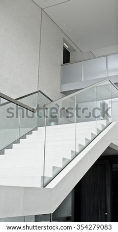 Part of a modern interior staircase with a glass bannister