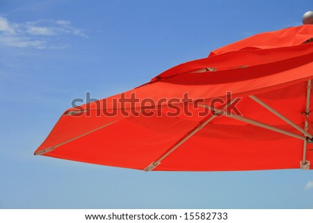 Part of a  orange umbrella and blue sky as background - stock photo