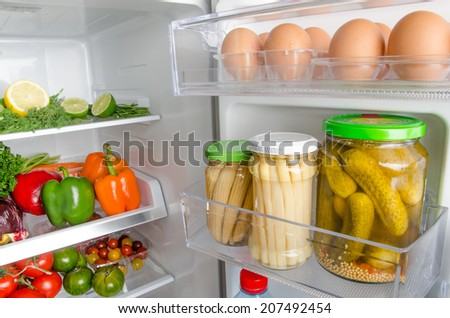 Part of a refrigerator full of different food products - stock photo