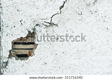 Part of a stone wall showing a hole with exposed wood - stock photo