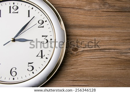 part of a wall clock on wooden background - stock photo