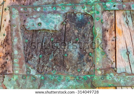 Part of a weathered ship wreck with old wooden planks and decayed metal - stock photo