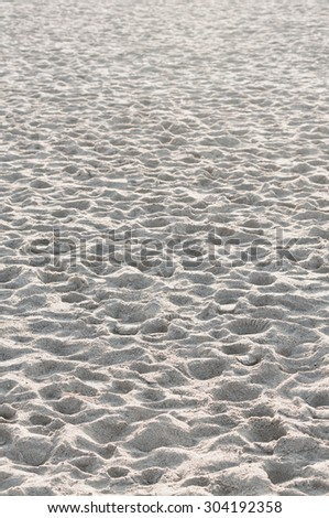 Part of a white sandy beach with many tracks - stock photo