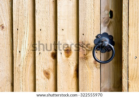 Part of  a wooden gate with a metal ring handle - stock photo