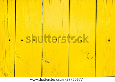 Part of a yellow painted fence as a background - stock photo
