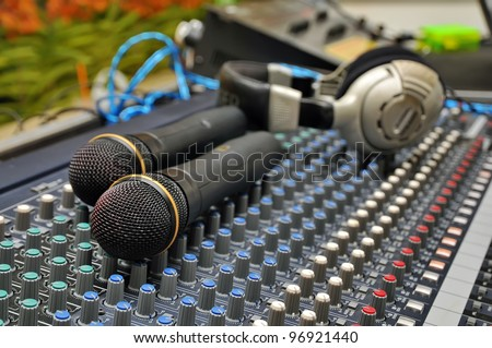 Part of an audio sound mixer with a microphone - stock photo