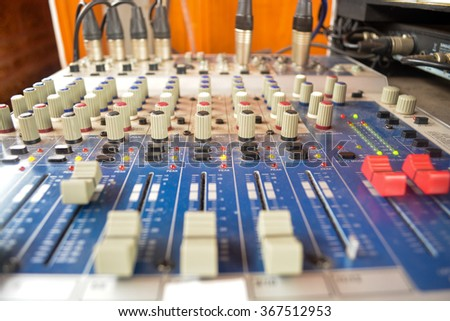 Part of an audio sound mixer with buttons and sliders .