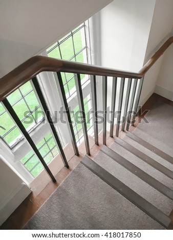 Part of an interior staircase with a wooden bannister - stock photo