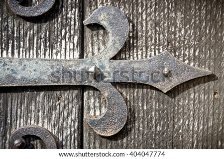 Part of an old metal hinge on a medieval wooden door - stock photo