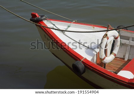 Part of an old red and white wooden boat on water