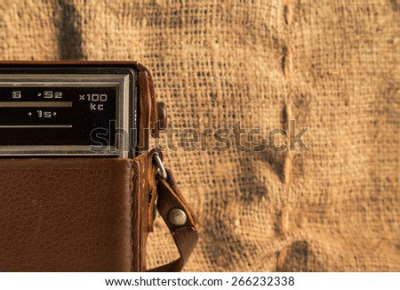 Part of an old transistor radio in a leather case on a background of a burlap. - stock photo