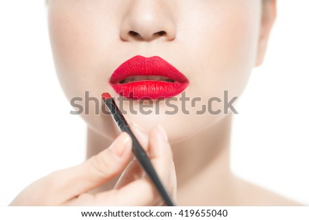 Part of attractive asian woman's face with fashion red lips makeup. Make-up artist apply bloody red lipstick