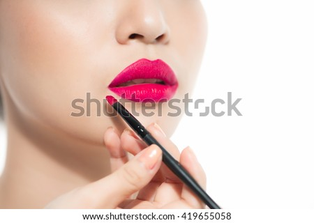 Part of attractive asian woman's face with fashion red lips makeup. Make-up artist apply pink lipstick - stock photo