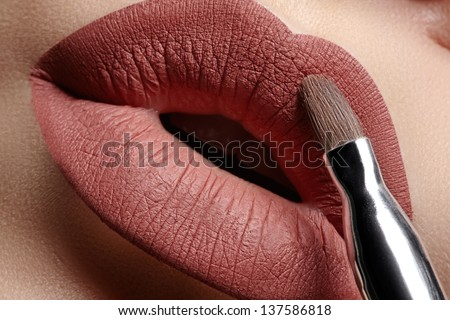 Part of attractive woman's face with fashion brown lips makeup. Professional make-up artist applying mat lipstick using cosmetic brush - stock photo