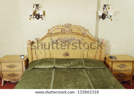 Part Of Bedroom Interior With Antique Bed, Nightstands And Wall Lamps - stock photo