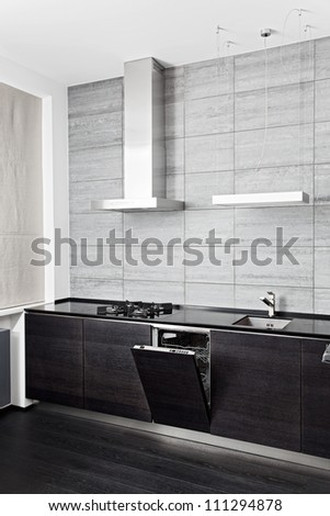 Part of black hardwood kitchen with build-in dish washer - stock photo