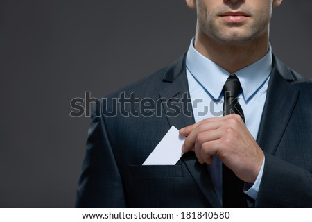Part of body of man who pulls out business card from the pocket of business suit, copyspace - stock photo