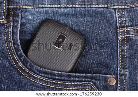 Part of cellphone in the front pocket of blue jeans - stock photo