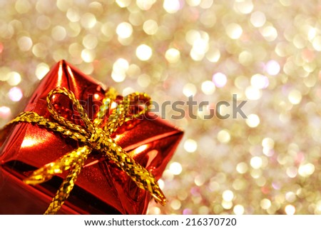Part of christmas red gift box with yellow bow on glitter silver and gold background  - stock photo