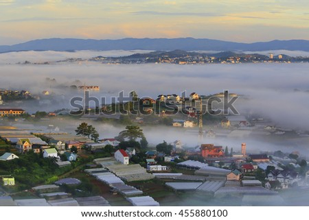 Part of Dalat city in Central highland of Vietnam on morning mist - stock photo
