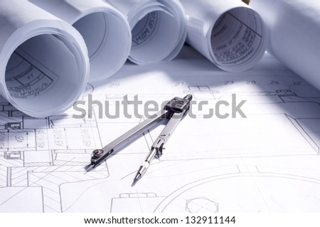 part of engineering project. rolls of blueprints and tools - stock photo