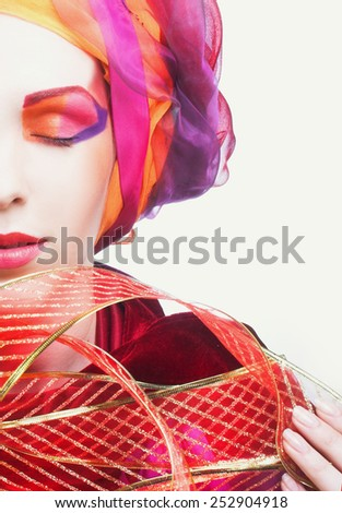 Part of face of the woman in pink and red turban and with artistic visage. - stock photo