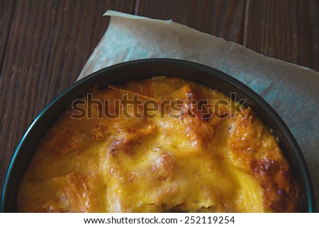 Part of homemade lasagna on wooden table - stock photo