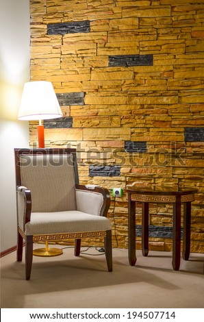 Part of interior - corner for rest; armchair, side table, lamp and stone wall - stock photo