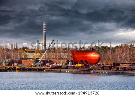 Part of large ship under construction on the background of a dramatic sky. - stock photo